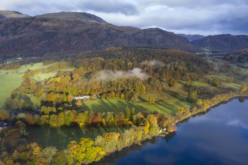 Breathtaking vibrant aerial drone landscape images over Coniston Water at sunrise on beautiful Autumn Fall morning royalty free stock photo