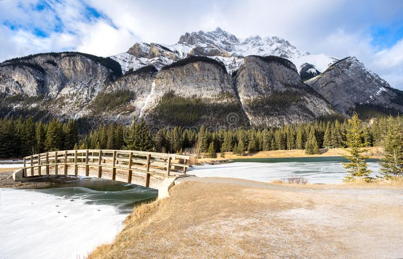 Breathtaking view of Cascade Mountain, Rocky Mountains, Canada,. Seen from park and quaint bridge at the bottom. Winter scene with snow capped peak royalty free stock photo