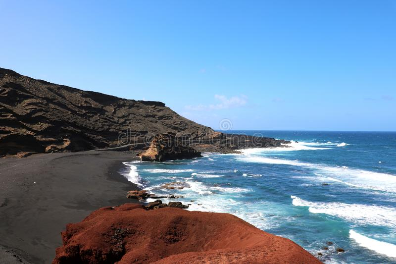 Breathtaking view of El Golfo bay: red ground, blue sea and black sand with volcanic mountains on background, Lanzarote. Canary Islands royalty free stock image