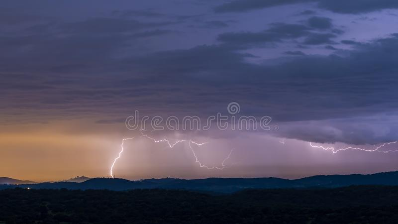 Powerful thunderstorm over hills at night. Breathtaking view of powerful thunderstorm over hills in dark evening stock images