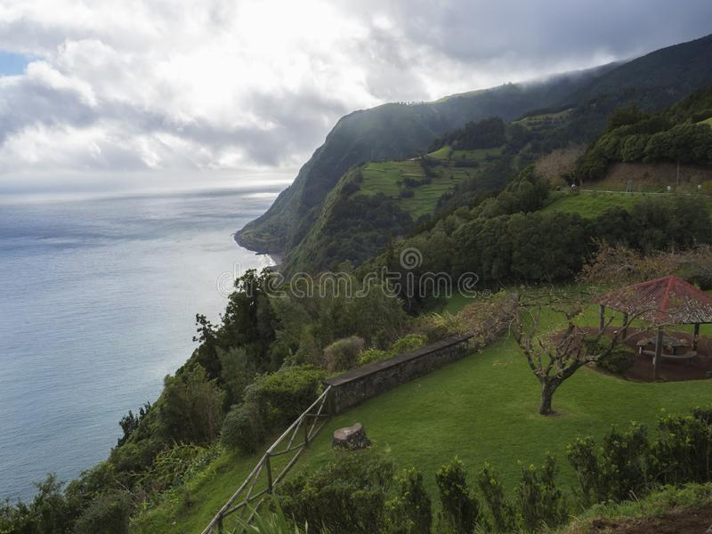 Breathtaking view with steep cliffs, sea, alcove and flower garden from the viewpoint Miradouro da Ponta do Sossego at. Breathtaking view with steep cliffs, sea stock images