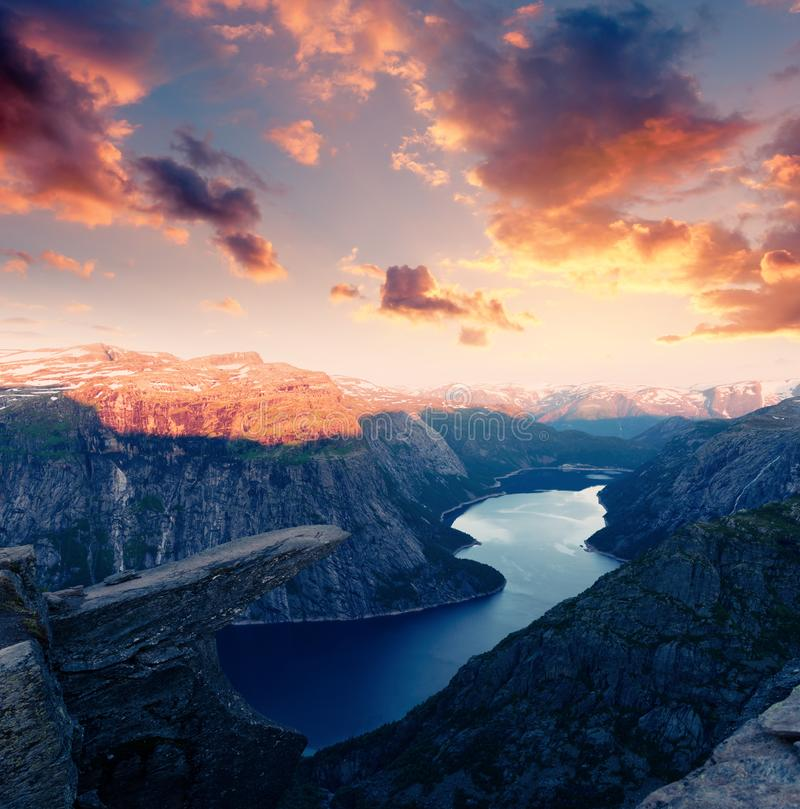 Breathtaking view of Trolltunga rock. Most spectacular and famous scenic cliff in Norway. Picturesque landscape with sunset sky and clear lake royalty free stock image