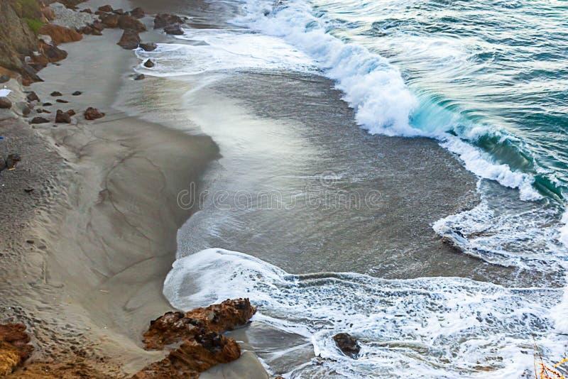 Brechen von tourqoise Welle auf dunklem sandigem beack mit Schaumspuren und -felsen stockbilder