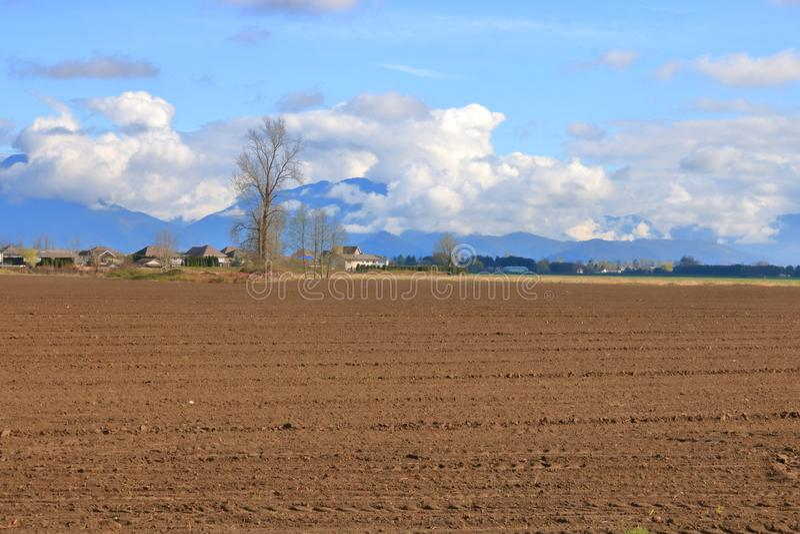 Bred öppen dal och plogat fält arkivbild