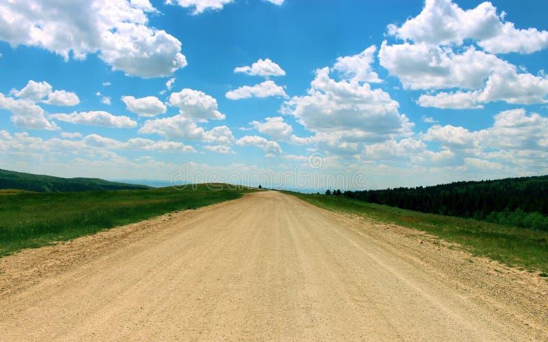Bred grusväg och härlig blå himmel royaltyfri bild
