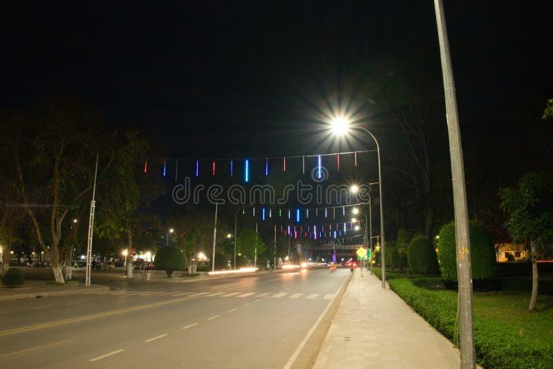Bred och rak gata av staden på natten som tänds av lyktor remsor f?r pilhorisontalmarkeringsv?g Dekorativa ljus ovanför vägen arkivbilder