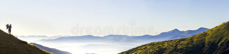 Bred panorama av morgonbergkullar och den ensamma fotvandrareturisten arkivbild