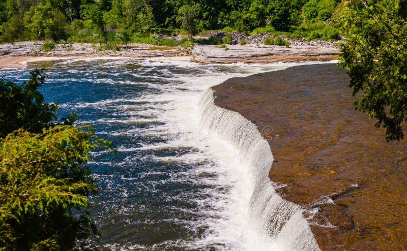 Bred plan vattenfall som flödar in i floden royaltyfria bilder