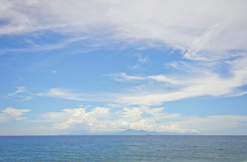 Bred sikt av ön av Bali och den Agung vulkan på horisonten från ön av Lombok i Indonesien arkivfoto