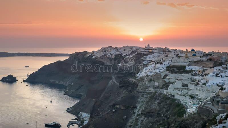 Bred sikt av solnedgången och byn av oia på santorini arkivfoton