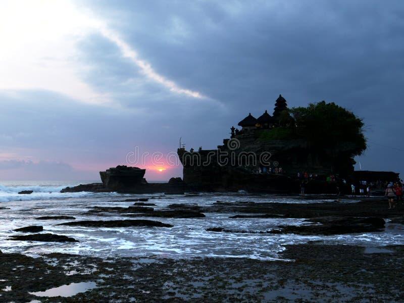 Bred sikt av tanahlotten på solnedgången under lågvatten på bali royaltyfria foton