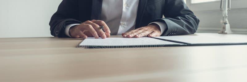Bred siktsbild av affärsmannen som sitter på hans kontorsskrivbord med p royaltyfri fotografi