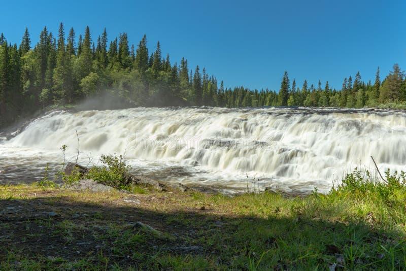 Bred vattenfall med slätt vatten i ljust sommarsolsken royaltyfria foton