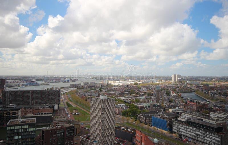 Bred vinkelöverblick på 100 metrar höjd över den Rotterdam horisonten med moln för blå himmel och vitregn arkivbild