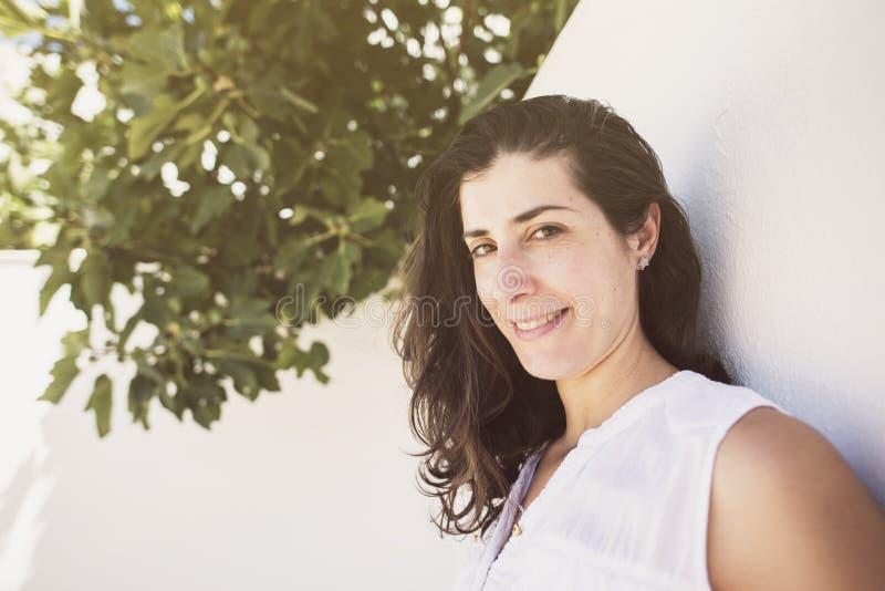 Bred vinkelkvinnastående nära till fikonträdtrre, i att le för uteplats royaltyfria foton