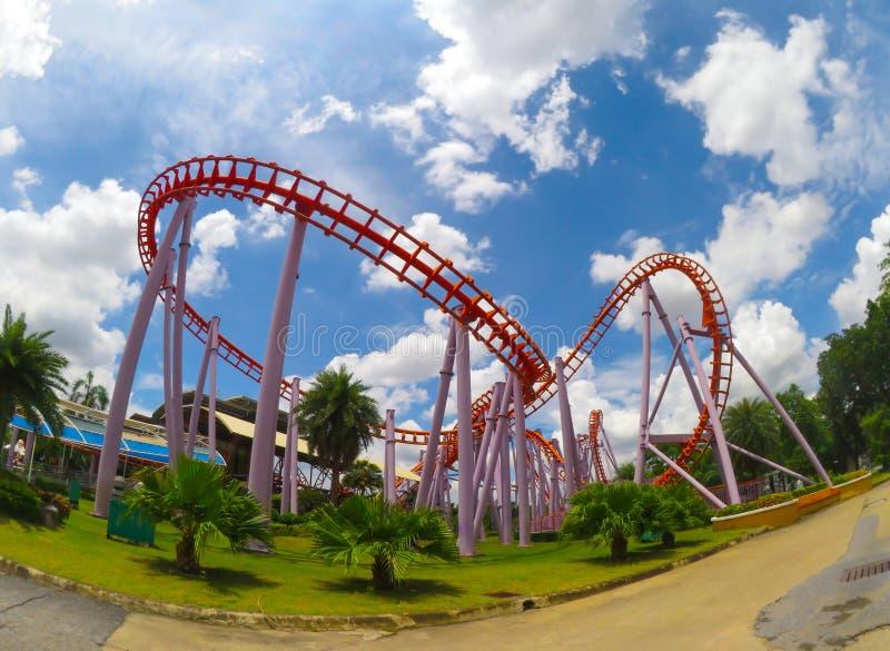 Bred vinkelsikt av det orange berg-och dalbanaspåret på det Siam Park City nöjesfältet med dag för molnig himmel arkivfoto