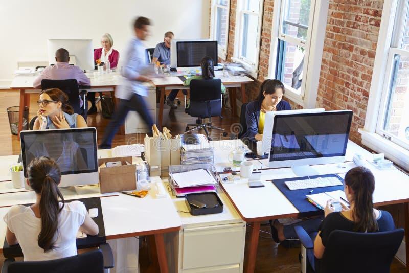 Bred vinkelsikt av det upptagna designkontoret med arbetare på skrivbord arkivfoto