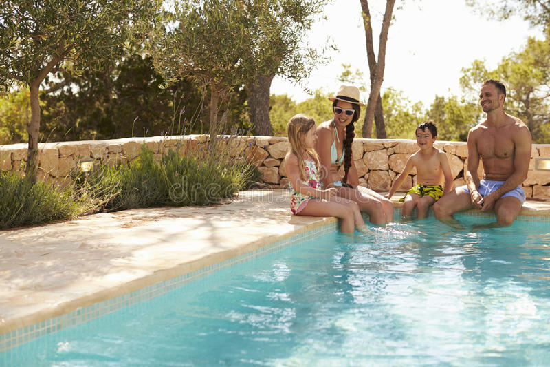 Bred vinkelsikt av familjen på semester som kopplar av vid pölen arkivfoton
