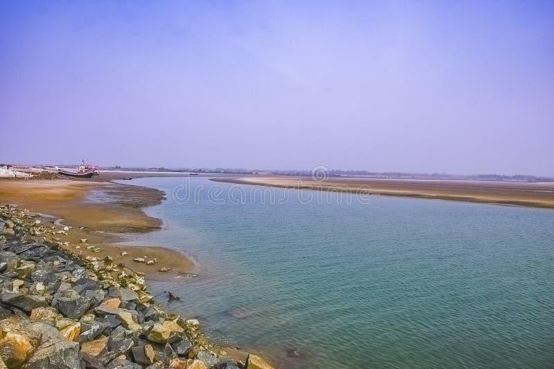 Breda flodmynningen munnen av en flod, uttag med ett fartyg på öst kostar Indien på soluppgången i en klar morgonvårtid arkivfoton