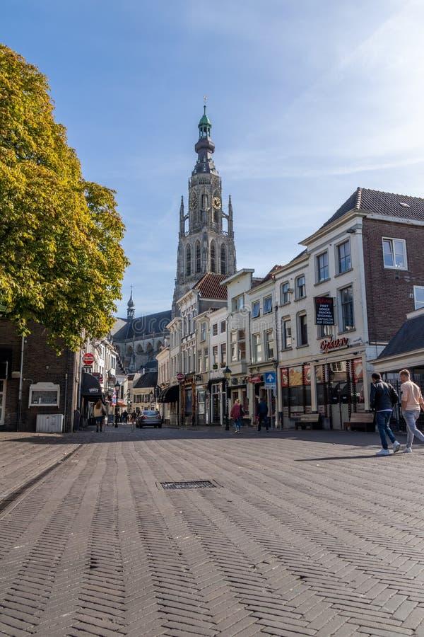 Breda, los Países Bajos - 29 de septiembre de 2018: Kerk de De grote situado en Breda central, con la gente y las tiendas en el p foto de archivo