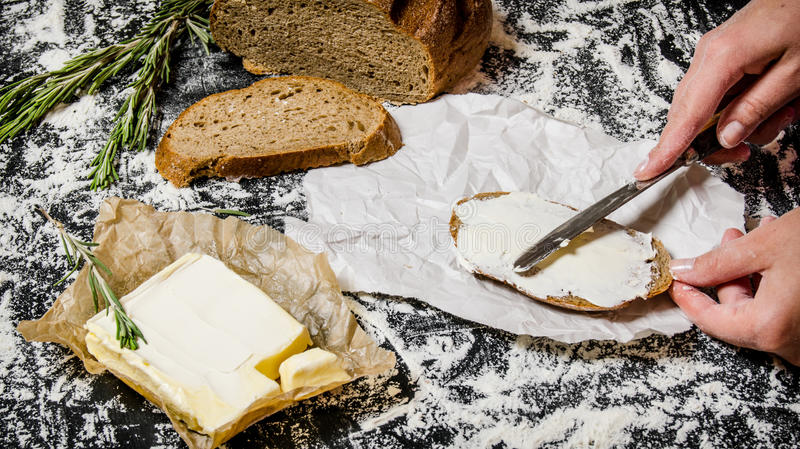 Breda smör på av bröd med smör arkivbild