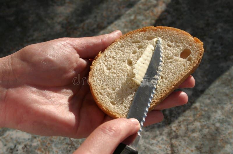 breda smör på för bröd arkivbilder