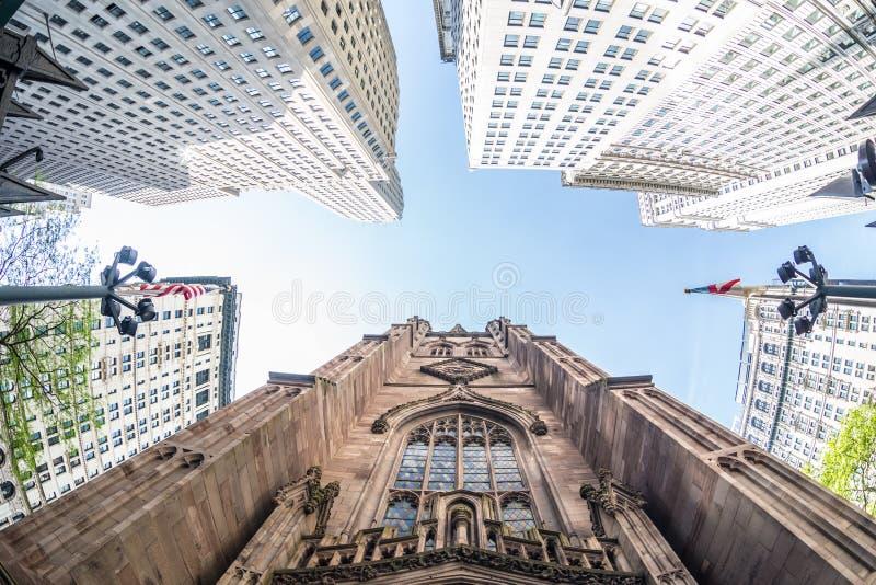 Brede hoek stijgende mening van Drievuldigheidskerk in Broadway en Wall Street met het omringen van wolkenkrabbers, Nieuw Lower M stock afbeeldingen