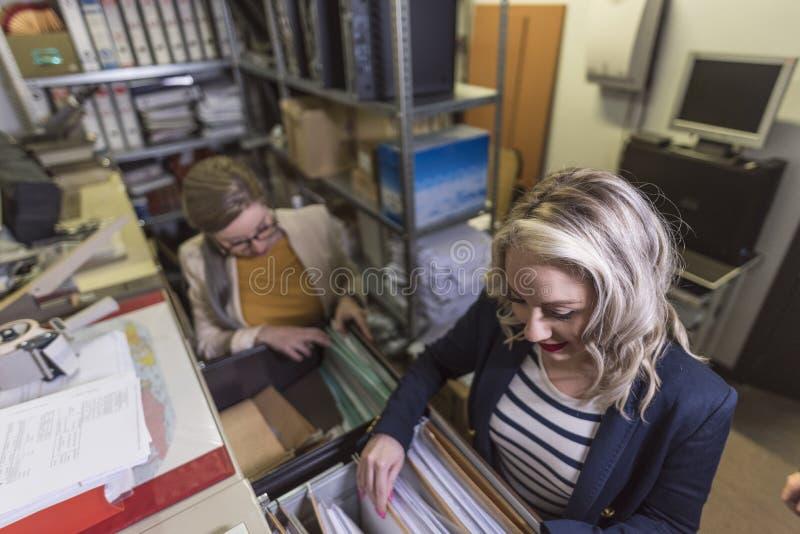 Brede hoek van het aantrekkelijke bureauvrouw werken die dossiers in kelderverdieping kijken stock fotografie