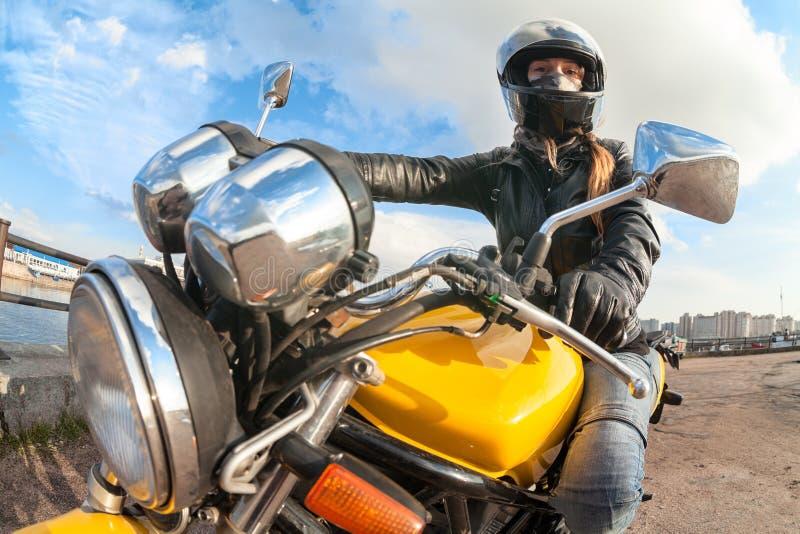 Brede hoekmening bij de jonge zitting van de vrouwenmotorrijder op fiets, nadruk op meisje royalty-vrije stock fotografie