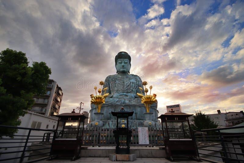 Brede hoekmening van Grote Boedha, Hyogo Daibutsu bij Nofukuji-Tempel met hemel, wolken en lichte avondzon, Kobe, Japan royalty-vrije stock fotografie
