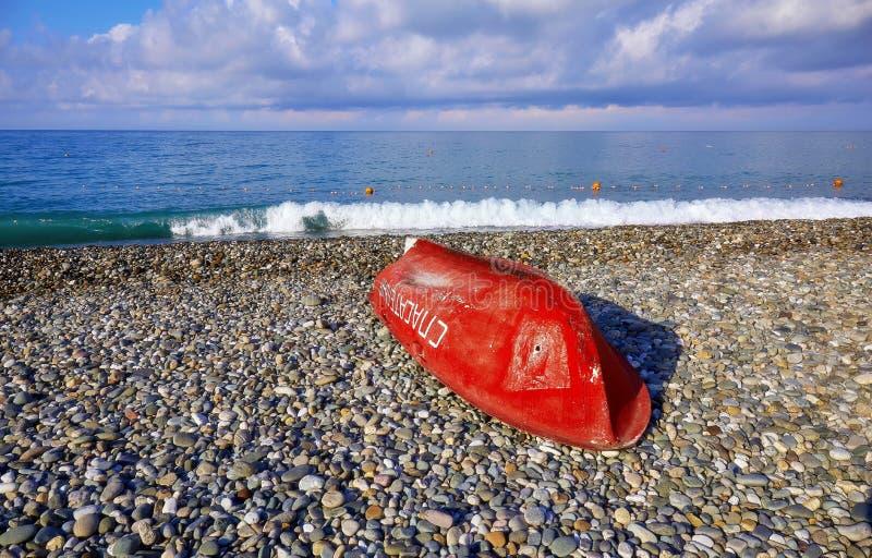 Brede hoekmening van rode boot op zonnig strand van de Zwarte Zee dichtbij Sotchi in de zomer stock afbeeldingen
