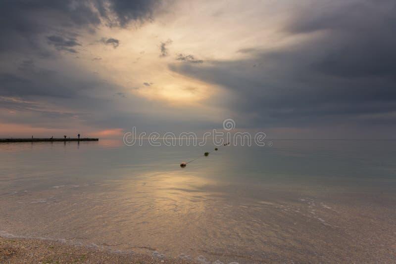 Brede hoekmening van vroeg ochtendzeegezicht met pijler op de achtergrond stock fotografie