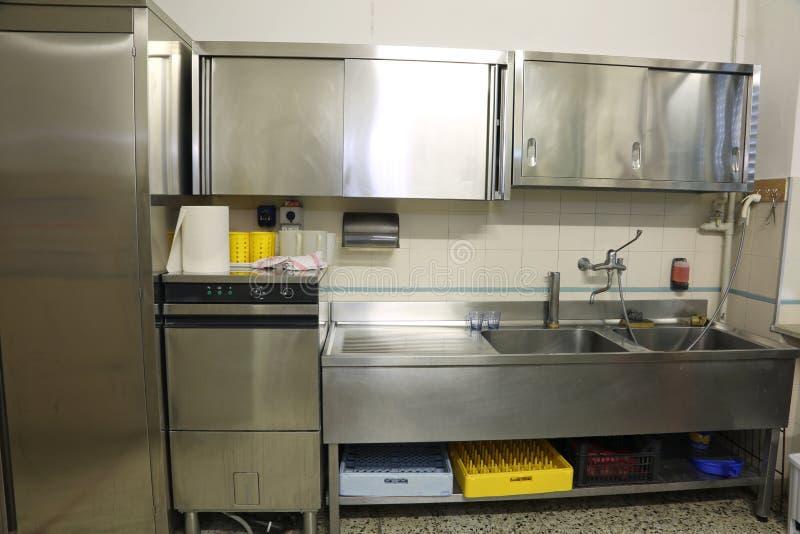 Brede keuken met grote staalgootsteen en industriële afwasmachine stock afbeelding