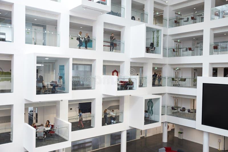 Brede mening van studenten in studiecellen op moderne universiteit stock foto