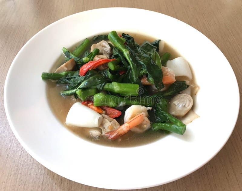 Brede rijstnoedel in romige jussaus met garnalen en pijlinktvis, RT stock foto's