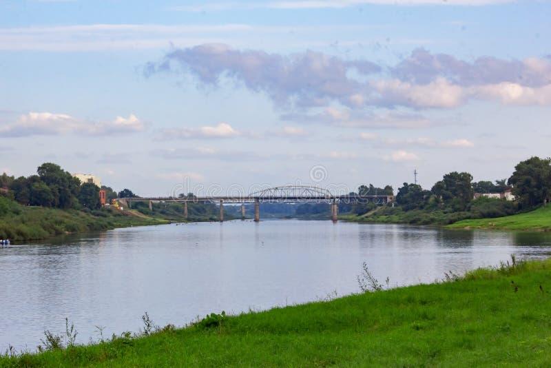 Brede rivier en brug, groene bank en bewolkte hemel royalty-vrije stock afbeelding