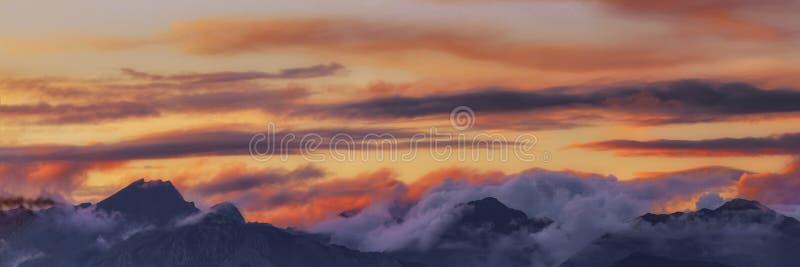 Brede van de het silhouetbos en berg van het hoekpanorama bovenkanten in de rode oranje blauwe zonsondergang van de wolkengradiën stock fotografie