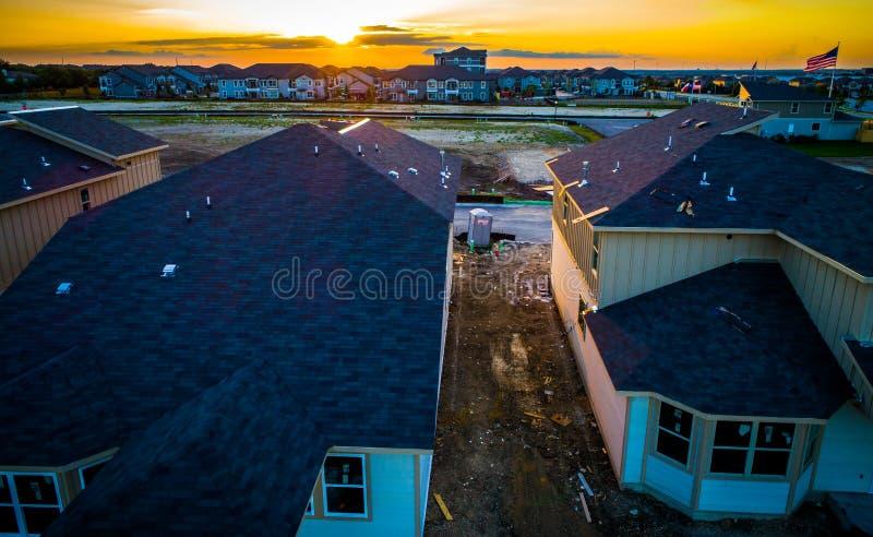Bredvid orange horisontsolnedgång för moderna tak strålar solen över konstruktionsförort för ny utveckling arkivfoto