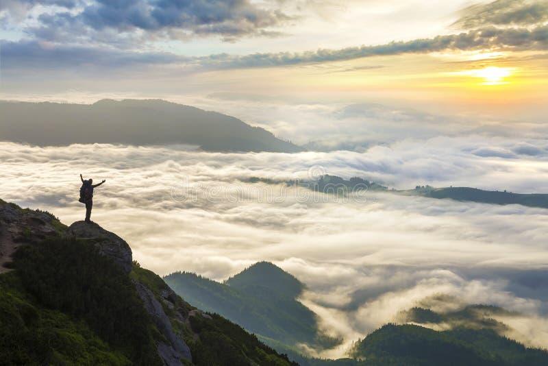 Breed bergpanorama Het kleine silhouet van toerist met rugzak op rotsachtige berghelling met opgeheven overhandigt behandelde val royalty-vrije stock afbeeldingen