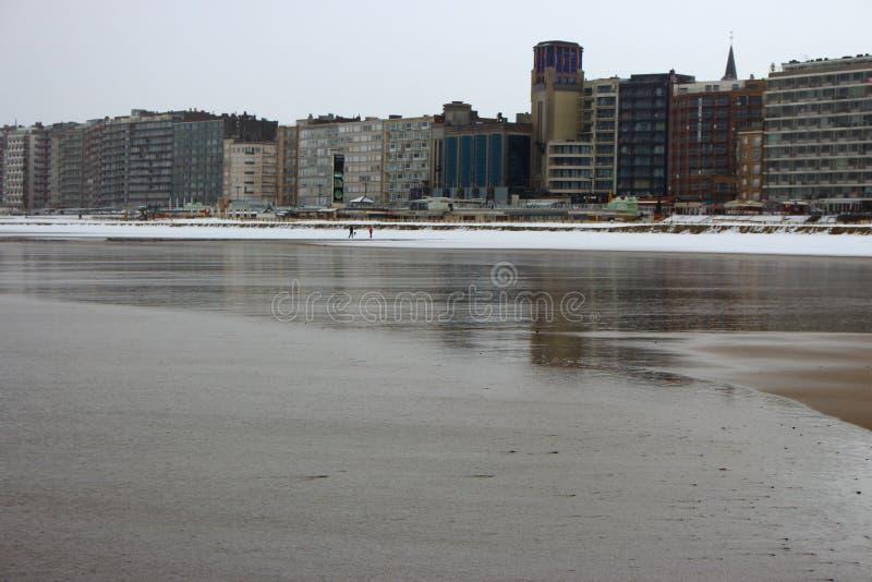Breed de winterstrand met natte zand en sneeuw en rij van huizen langs zeekust op bewolkte dag Moderne architectuur op kust royalty-vrije stock afbeeldingen