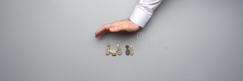 Breed meningsbeeld die van mannelijke hand beschermend die gebaar over een familie maken van kiezelstenen wordt gemaakt royalty-vrije stock foto's