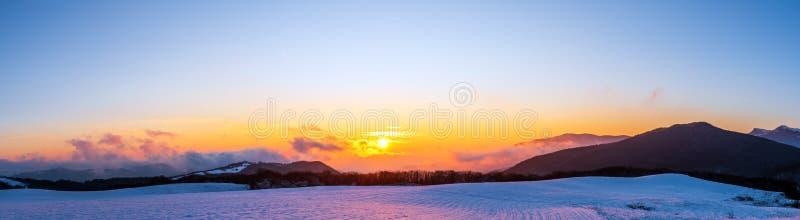 Breed panorama van mooie trillende de winterzonsondergang in bergen stock afbeelding
