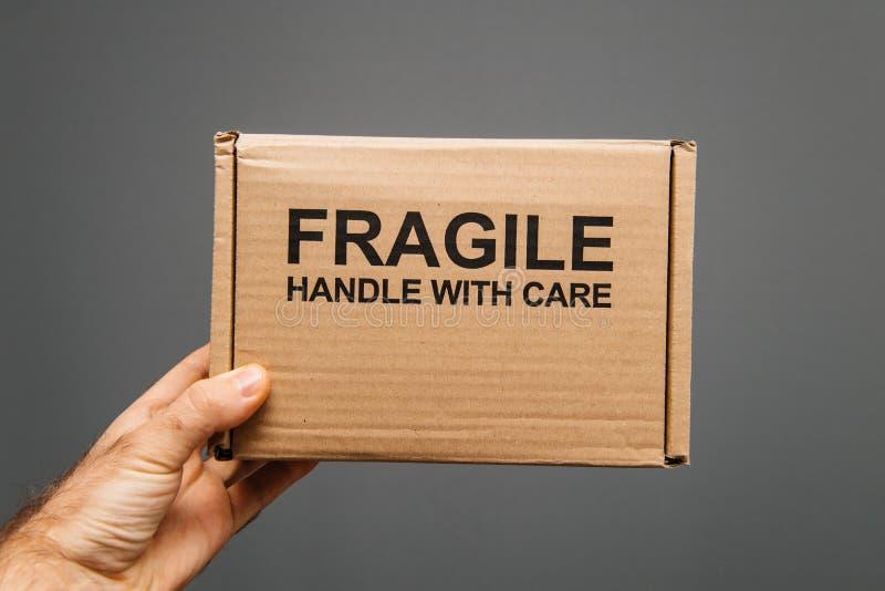 Breekbaar handvat met de doos van het zorgkarton in mannelijke ge?soleerde hand stock afbeelding