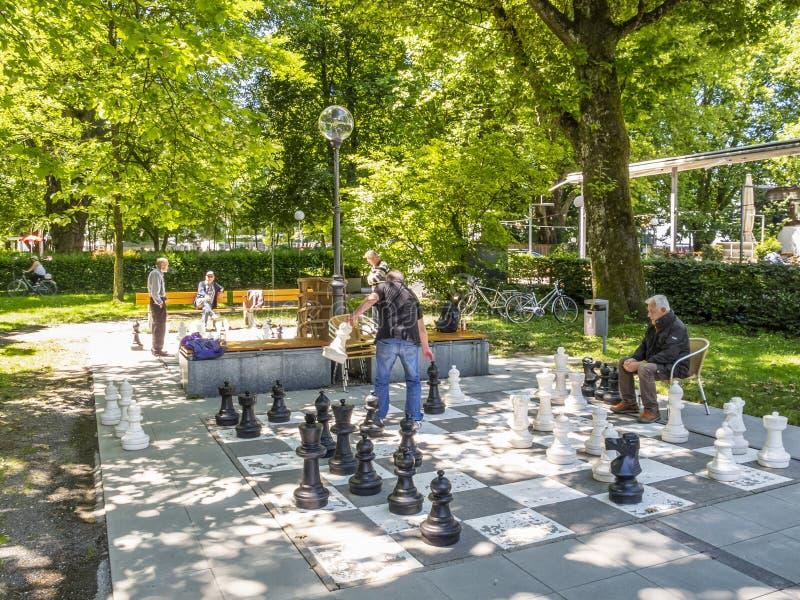 BREGENZ, AUSTRIA - 24 GIUGNO 2015: Gli uomini non identificati giocano gli scacchi con i pezzi degli scacchi giganti sul lago di  fotografia stock