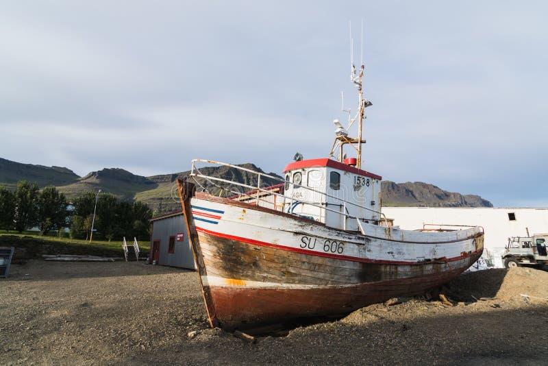 BREIDDALSVIK, ISLANDA - AGOSTO 2018: vecchia condizione abbandonata del peschereccio sulla terra accanto alla fabbrica di birra d immagine stock libera da diritti