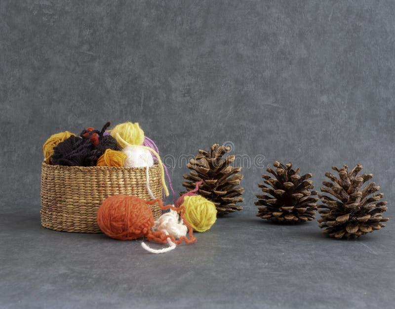 Breiend of haak dalingsbeeld Een dalingsdecor met ballen van wol in een mand en denneappels stock afbeeldingen