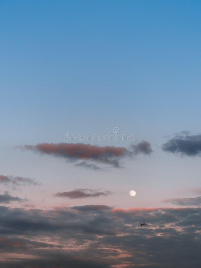 Breit-Körperflugzeugdurchläufe durch den Vollmond bei Sonnenuntergang lizenzfreie stockbilder