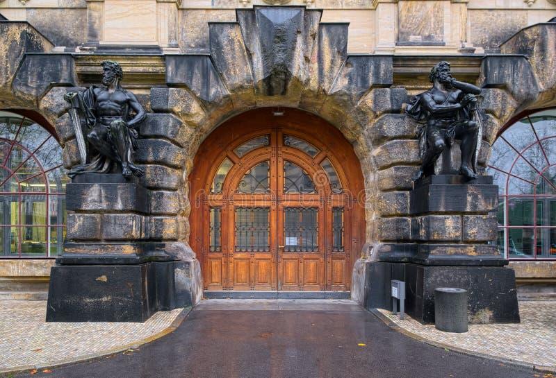 Breite Holztür gestaltet durch Statuen stockfotografie