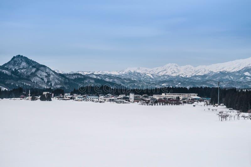 Breite Landschaft des kleinen Dorfs und des Gebirgszugs in Fukushima, stockfotografie