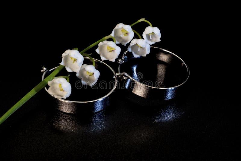 Breite Ohrringe der glänzenden Runde Metallund weiße Maiglöckchenblume stockfoto